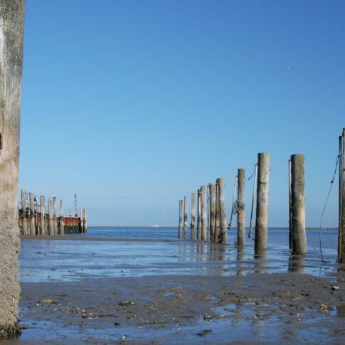 Wie ein Spalier stehen die Dalben im leeren Hafen; erst  bei Flut kann wieder ein Schiff kommen