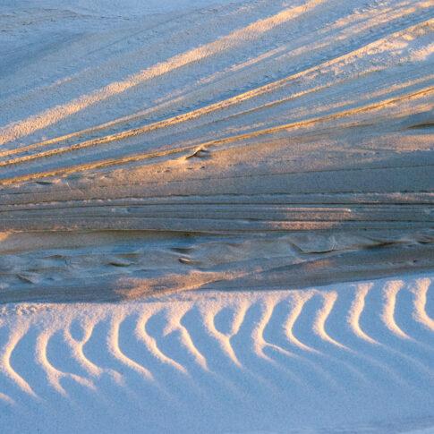 Die graphischen Muster im Dünensand sind nur durch Windkraft entstanden; die Abendsonne macht daraus ein Licht- und Schattenbild.