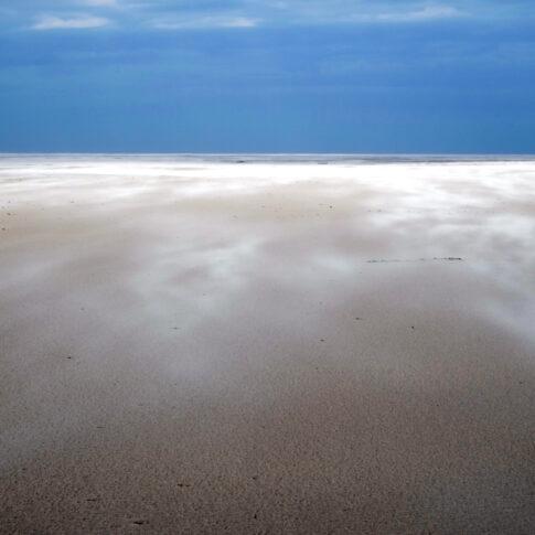 Sturmgebraus treibt losen Sand über den feuchten Kniepsand