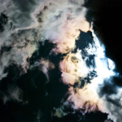 Sonne und Wolken spiegeln sich im Wasser, Spektralfarben erscheinen
