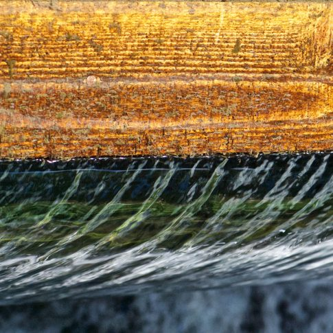 Mariella Knabe - Schwerkraft - Wasser fließt über ein Holzschott aus einem Teich ab