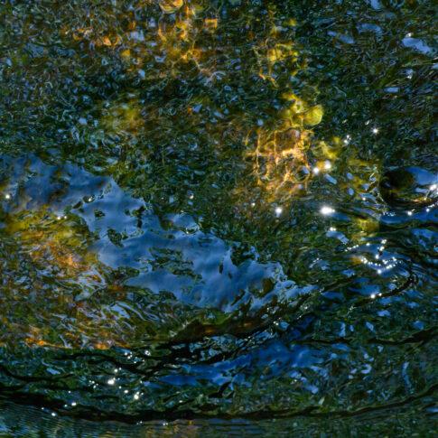Die Farben des Saphirs, eingefroren in Wasser über Felsen. Himmelsblau und Baumgrün spiegeln sich darin.